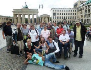Das Bild zeigt eine Reisegruppe in Berlin vor dem Brandenburger Tor.
