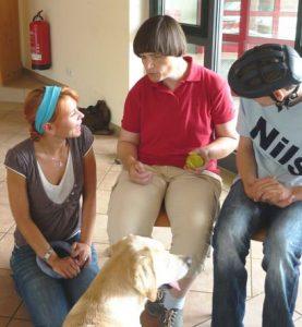 Das Bild zeigt eine Therapeutin mit ihrem Hund und zwei Menschen mit Behinderung.