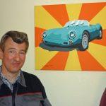 Das Bild zeigt einen Mitarbeiter mit dem Bild eines Sportwagens, das er gemalt hat.