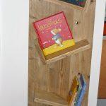 Das Bild zeigt ein asymmetrisches Bücherregal mit bunten Bilderbüchern.