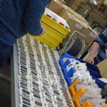 Das Bild zeigt einen Mitarbeiter beim Sortieren verpackter Pflaster.