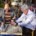 Das Bild zeigt zwei Männer, die Steine bearbeiten.