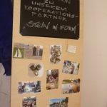Das Bild zeigt eine Schauwand mit Fotos einer Exkursion zu einem Steinmetz.
