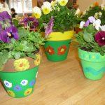 Das Bild zeigt bunt bemalte Blumentöpfe mit Stiefmütterchen.