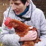 Das Bild zeigt eine bewohnerin mit einem Huhn auf dem Arm.