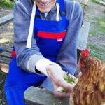 Das Bild zeigt einen der Bewohner beim Füttern eines Huhns.