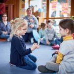 Ein Kind spricht mit einem anderen Kind in Gebärdensprache.