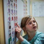Das Bild zeigt ein Mädchen, das auf Symbole der Unterstützten Kommunikation zeigt.
