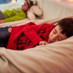 Das Bild zeigt zwei Kinder, die im Snoezelraum entspannen.