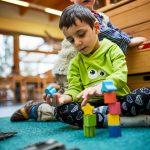 Das Bild zeigt einen Jungen, der mit Bauklötzen spielt.