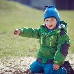 Das Bild zeigt einen warm gekleideten Jungen, der Sand aus seiner Hand rieseln lässt.
