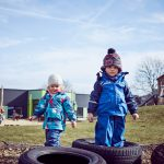 Das Bild zeigt zwei Kinder beim Spielen auf dem Außengelände.