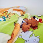 Das Bild zeigt ein Stofftier, das in einem bunt bezogenen Bett liegt.