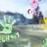 Das Bild zeigt ein Fenster mit Handabdrücken und Namen aus bunten Farben.