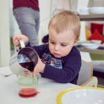 Das Bild zeigt einen kleinen Jungen, der vorsichtig ein Getränk in ein Glas füllt.