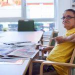 Das Bild zeigt einen der Bewohner, der am Tisch sitzt und die Zeitung liest.