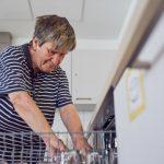 Das Bild zeigt, wie eine Bewohnerin Geschirr in die Spülmaschine räumt.