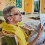 Das Bild zeigt einen Klienten, der Zeitung liest.