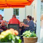 Das Bild zeigt einige Bewohner beim Kaffeetrinken auf der Terrasse.