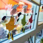 Das Bild zeigt eine bunte Fensterdekoration mit tanzenden Kühen.