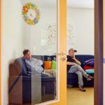 Das Bild zeigt zwei Bewohner, die auf einem Sofa sitzen.