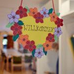 """Das Bild zeigt ein gebasteltes Herz aus buntem Papier mit dem Schriftzug """"Willkommen""""."""