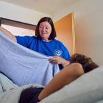 Das Bild zeigt eine Pflegekraft, die eine Klientin zudeckt.