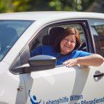 Das Bild zeigt die Leiterin des Pflegedienstes in ihrem Dienstwagen.