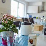 Das Bild zeigt einen Esstisch mit einer Topfpflanze und Gläsern und Tassen.