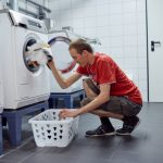 Das Bild zeigt einen jungen Mann, der Wäsche in eine Waschmaschine steckt.
