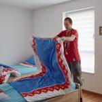 Das Bild zeigt einen jungen Mann, der sein Bett macht.
