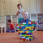 Das Bild zeigt einen JUngen, der ein riesiges Fahrzeug aus Legosteinen gebaut hat.