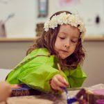 Das Bild zeigt ein Mädchen mit einem Blumenkranz auf dem Kopf beim Malen.