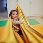 Das Bild zeigt ein lachendes Mädchen in einer Tuchschaukel.