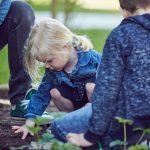 Das Bild zeigt Kinder, die im Blumenbeet arbeiten.
