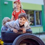 Das Bild zeigt drei Kinder, die mit großen Autoreifen spielen.