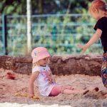 Das Bild zeigt zwei Mädchen, die im Sand spielen.