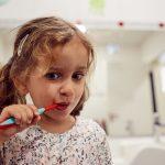 Das Bild zeigt ein Mädchen, das sich die Zähne putzt.