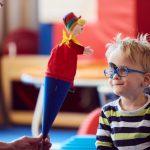 Das Bild zeigt eine Therapeutin, die einem kleinen Jungen eine bunte Handpuppe zeigt.
