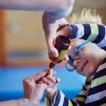 Das Bild zeigt einen kleinen Jungen, der den Zeigefinger in eine kleine Glasflasche steckt.