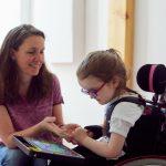 Das Bild zeigt eine Therapeutin und ein Mädchen mit einem Talker.