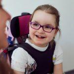 Das Bild zeigt ein lachendes Mädchen im Rollstuhl.