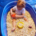 Das Bild zeigt ein Kind, das in einer mit getrockneten Bohnen gefüllten Plastikwanne sitzt.