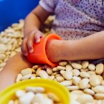 Das Bild zeigt ein Kind, dass mit getrockneten Bohnen spielt.