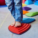 Das Bild zeigt die Füße eines Kindes auf einem kleinen Gymnastikpodest.