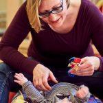 Das Bild zeigt eine Therapeutin, die sich mit einem Baby beschäftigt.