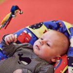 Das Bild zeigt ein Kind, das sich eine bunte Handpuppe anschaut.