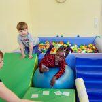 Das Bild zeigt zwei Kinder und eine Therapeutin mit einem Kartenspiel.