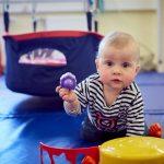 Das Bild zeigt ein Kleinkind, das eine violette Plastikfigur in der Hand hält.