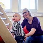 Das Bild zeigt ein Kleinkind, das eine Leiter erklimmt.